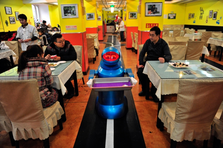 Image: Robot that specialises in delivering food holds an empty plate after serving meals to customers at a Robot Restaurant in Harbin